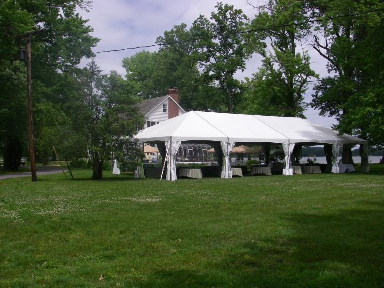 Wedding reception tent, faerie lights, tulle, flowers, party favors, and plentiful tables.