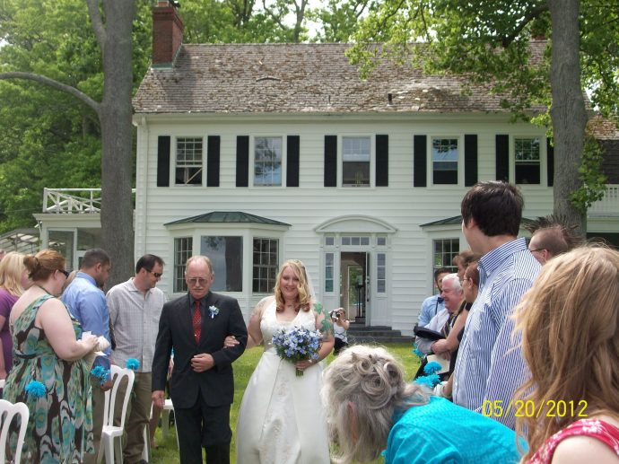 The father of the bride walks her down the aisle at Bayfields Bed and Breakfast