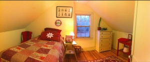 Rapunzel, the 3rd floor guest room at Bayfields Bed and Breakfast, showing off it's red and white theme, has a warm glow at dusk.